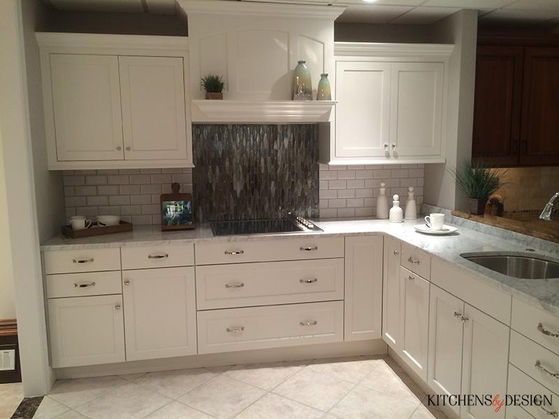 grey and white L-shaped kitchen with custom tile backsplash