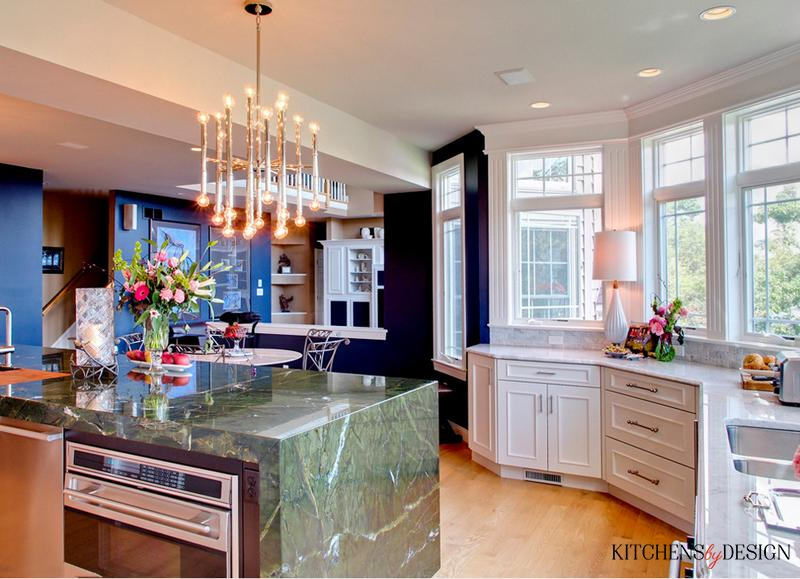 unique style kitchen with chandelier, green island and stainless steel appliances