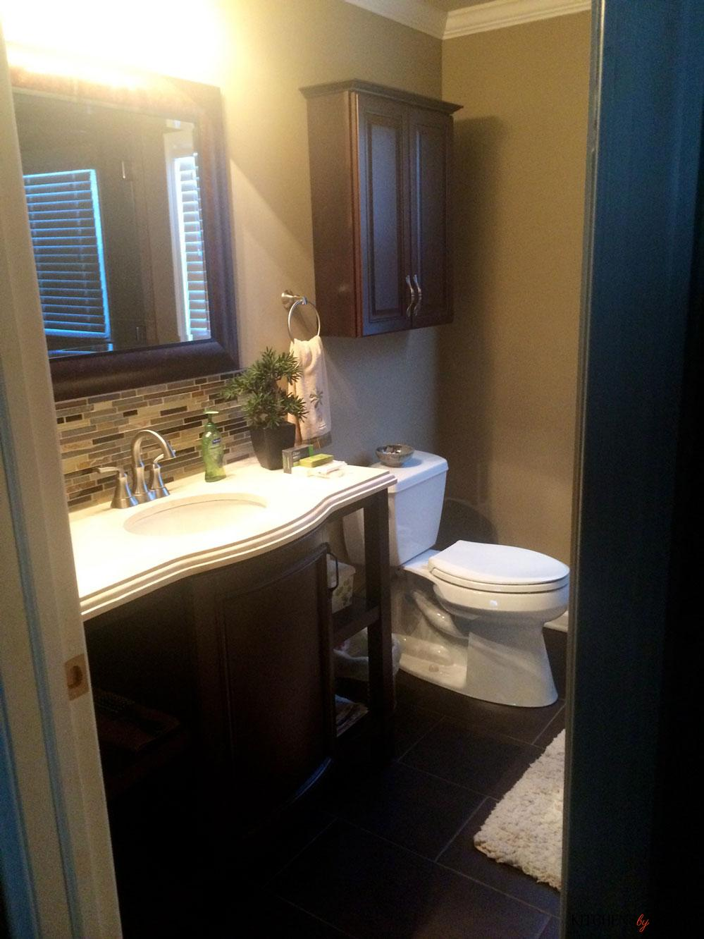 coffee colored bath with custom tiling accent above sink